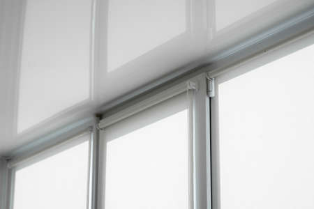 White fabric roller blinds on the plastic window on a balcony in the living room with a reflection in a stretch ceiling.
