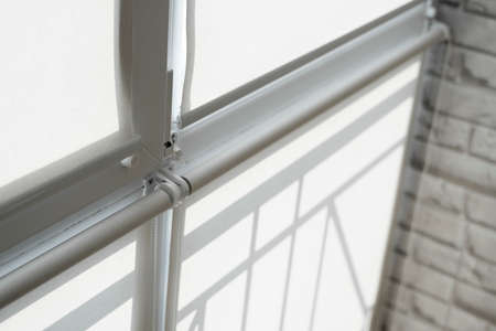 White fabric roller blinds on the plastic window on a balcony in the living room.