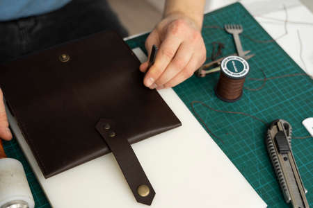 Mens hand working on the leather wallet in his workshop. Working process with a brown natural leather. Craftsman holding a crafting tools. Reklamní fotografie