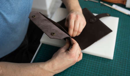 Mens hand working on the leather wallet in his workshop. Working process with a brown natural leather. Craftsman holding a crafting tools.