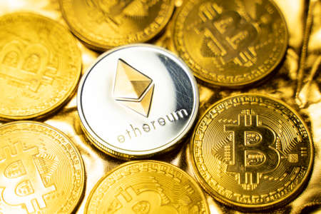 Gold ethereum coins among bitcoins on a golden background. Trading on the cryptocurrency exchange. Cryptocurrency Stock Market Concept. Virtual money concept. Mining or blockchain technology. Stock Photo