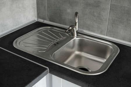 Stainless steel kitchen sink on a dark grey granite worktop. Kitchen sink and water tap in the kitchen. 免版税图像