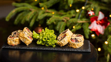 Custom sushi roll in tempura with nori, fresh salmon, tuna, avocado, masago caviar, drizzled with pineapple sauce with salad pouring as decoration on a black plate on a wooden table for Christmas. 免版税图像