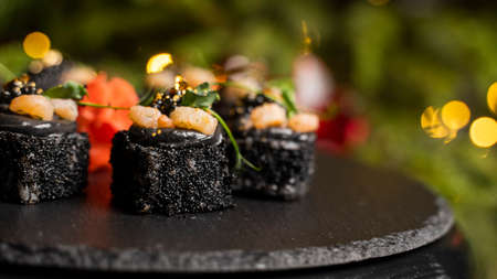 Sushi with black rice, crab meat, avocado, smoked salmon mousse, oar caviar, masago, shrimp cocktail and edible gold leaf with ginger on black table for Christmas with a Christmas tree on background. Archivio Fotografico