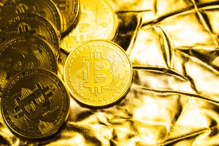 Golden bitcoin Coins on a golden background. Trading on the cryptocurrency exchange. Cryptocurrency Stock Market Concept. Virtual money concept. Mining or blockchain technology. Business concept.