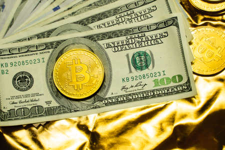 Golden bitcoin coins with a dollars on a golden background. Trading on the cryptocurrency exchange. Cryptocurrency Stock Market Concept. Mining or blockchain technology. Business concept.