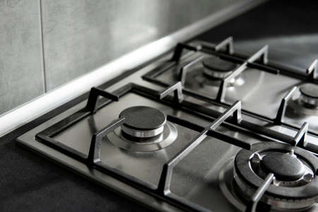 Stainless grey metal kitchen gas stove installed on a the kitchen with a dark grey table top.
