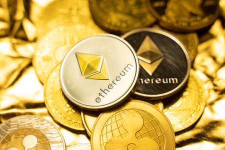 Gold ethereum coins on a golden background among another crypto coins. Trading on cryptocurrency exchange. Cryptocurrency Stock Market Concept. Virtual money concept. Mining blockchain technology. 免版税图像