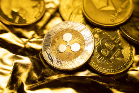 Gold Ripple coins on a golden background. Trading on the cryptocurrency exchange. Cryptocurrency Stock Market Concept. Virtual money concept. Mining or blockchain technology. Business concept.