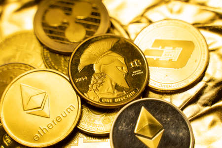 Gold crypto coins on a golden background. Trading on the cryptocurrency exchange. Cryptocurrency Stock Market Concept. Virtual money concept. Mining or blockchain technology. Business concept.