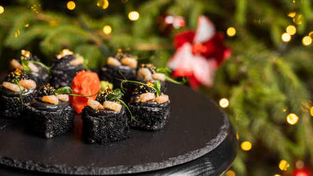 Sushi with black rice, crab meat, avocado, smoked salmon mousse, oar caviar, masago, shrimp cocktail and edible gold leaf with ginger on black table for Christmas with a Christmas tree on background.