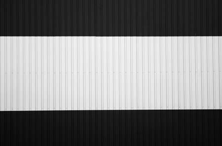 Black and white corrugated iron sheet used as a facade of a warehouse or factory. Texture of a seamless corrugated zinc sheet metal aluminum facade. Architecture. Metal texture. 写真素材