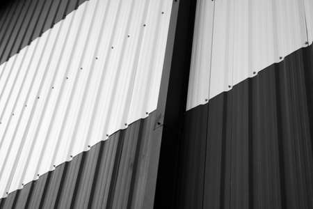Details of black and white corrugated iron sheet used as a facade of a warehouse or factory. Texture of a seamless corrugated zinc sheet metal aluminum facade. Architecture. Metal texture.