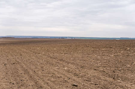 A pure plowed field under the cloudy sky. 写真素材