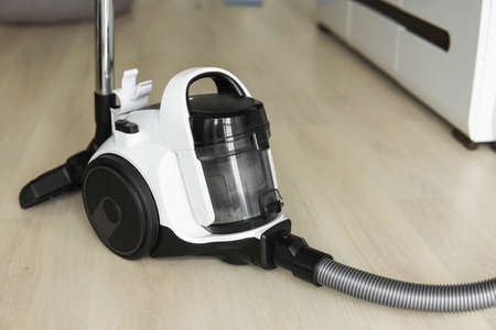 Bagless cyclone vacuum cleaner on a laminate. Electrical apparatus that by means of suction collects dust and small particles from floors and other surfaces.