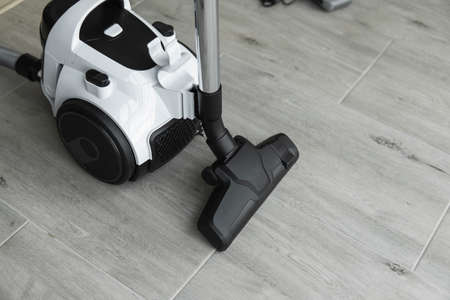 Bagless cyclone vacuum cleaner on a grey tile. Electrical apparatus that by means of suction collects dust and small particles from floors and other surfaces. 写真素材