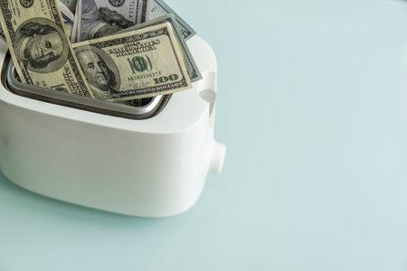 US Hundred dollar bills burning in the toaster. US dollars roasting in toaster. Financial concept. 免版税图像