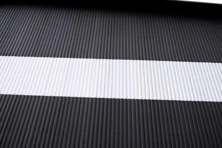 Black and white corrugated iron sheet used as a facade of a warehouse or factory. Texture of a seamless corrugated zinc sheet metal aluminum facade. Architecture. Metal texture. 免版税图像