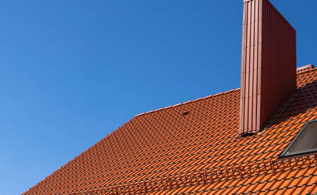 Red corrugated metal profile roof installed on a modern house. The roof of corrugated sheet. Roofing of metal profile wavy shape. Modern roof made of metal. Metal roofing. 写真素材