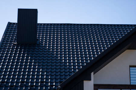 Grey corrugated metal profile roof installed on a modern house. The roof of corrugated sheet. Roofing of metal profile wavy shape. Modern roof made of metal. Metal roofing.