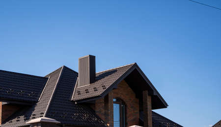 Brown corrugated metal profile roof installed on a modern house. The roof of corrugated sheet. Roofing of metal profile wavy shape. Modern roof made of metal. Metal roofing. 写真素材