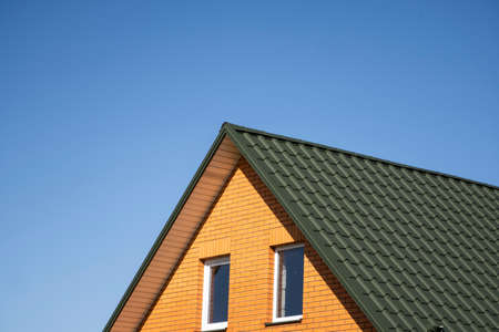 Green corrugated metal profile roof installed on a modern house. The roof of corrugated sheet. Roofing of metal profile wavy shape. Modern roof made of metal. Metal roofing.