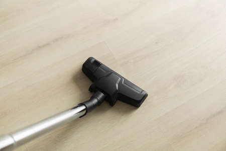 Top view of head of modern vacuum cleaner cleaning a laminate.