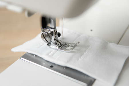 Sewing machine with with a white cloth on a wooden table. 免版税图像