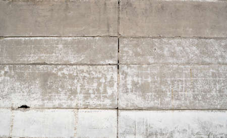 Old grungy grey concrete wall texture with a holes and seams. 免版税图像