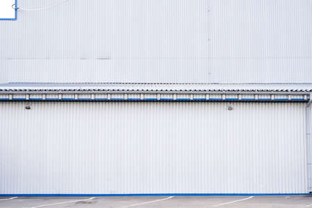 White corrugated iron sheet used as a facade of a warehouse or factory. Texture of a seamless corrugated zinc sheet metal aluminum facade. Architecture. Metal texture.