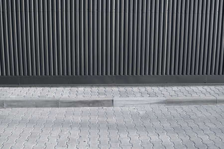 Brick pavement tile on a street near industrial building. Urban texture as background. 免版税图像