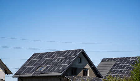 Modern solar panels on house roof in a sunny day. 免版税图像