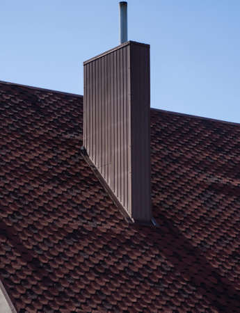 Brown corrugated metal profile roof installed on a modern house. The roof of corrugated sheet. Roofing of metal profile wavy shape. Modern roof made of metal. Metal roofing. 免版税图像