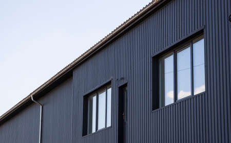 Black corrugated iron sheet used as a facade of a warehouse or factory with a windows. Texture of a seamless corrugated zinc sheet metal aluminum facade. Architecture. Metal texture.
