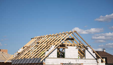 Wooden roof construction against blue sky. House building.