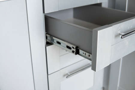 Stainless telescopic bayonet drawer slide guides, installed on a kitchen cabinet from gray chipboard. Accessories for carpentry used in the construction of furniture. Custom kitchen installation.