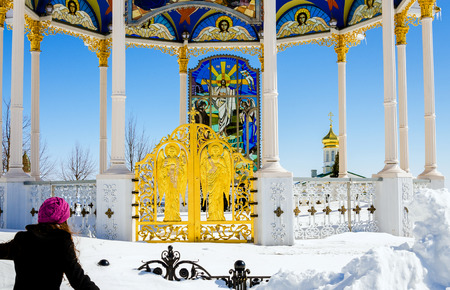 adherent: Flying to god. Girl is flying to summer altar in the Pochaev lavra throuth very big snowdrift. Editorial