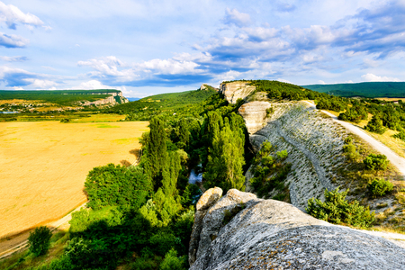 Valley of river in mountain. The riverbed flows between rocky mountain and the field. Stock Photo