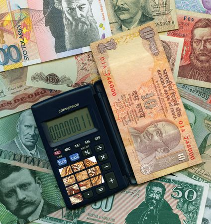 Calculator and coins with paper banknotes from around the world.  photo