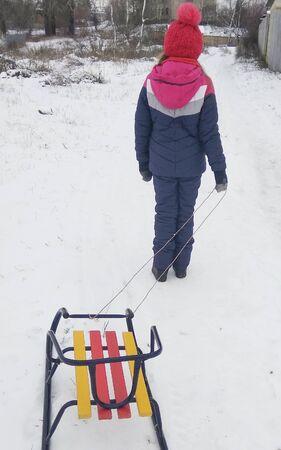girl go sledding downhill