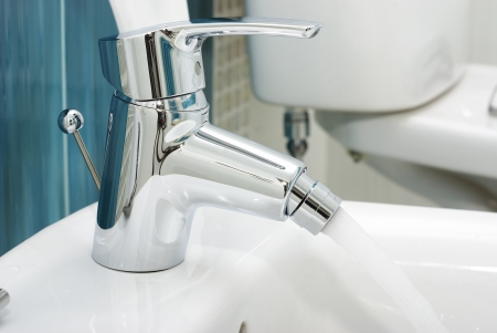 White toilet bidet object in a clean room with a metal faucet photo