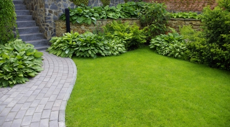 landscape garden: Garden stone path with grass growing up between the stones  Stock Photo