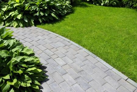Tuin stenen pad met gras groeien tussen de stenen Stockfoto