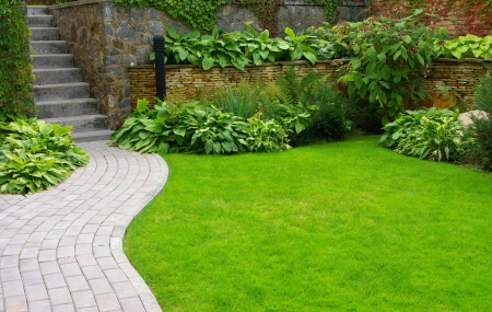 Garden stone path with grass growing up between the stones  Stock Photo