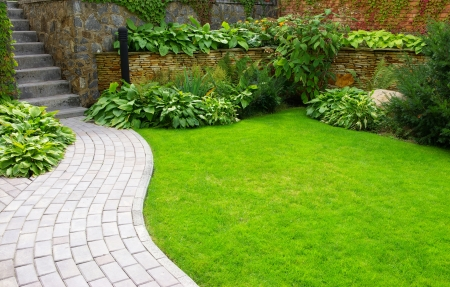 garden landscape: Garden stone path with grass growing up between the stones  Stock Photo