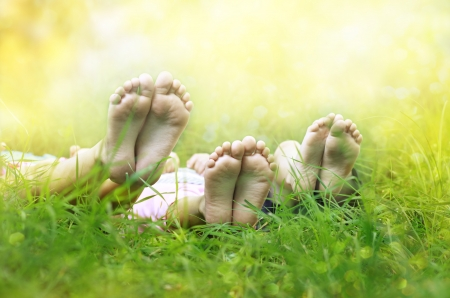 boy feet:  Happy children lying on green grass