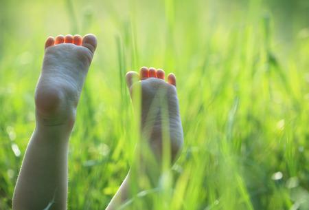 pies descalzos: Niños felices que mienten en hierba verde