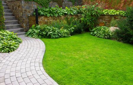 Tuin stenen pad met gras groeit tussen de stenen Stockfoto