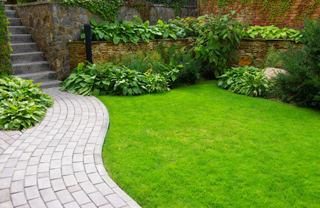 Garden stone path with grass growing up between the stones photo