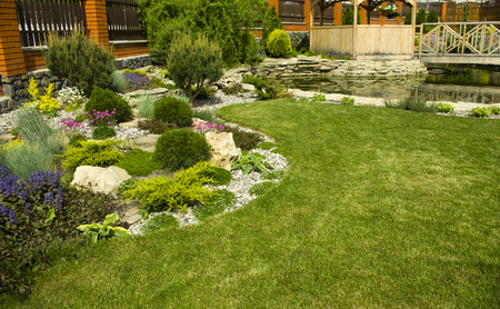arbor: Arbor in garden with flowerbed, colorful plants and pond